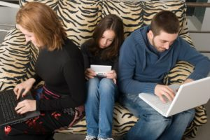 Family absorbed in new technology, showing the failure of communication between them