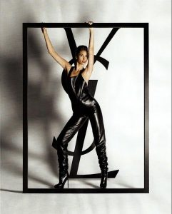woman dressed in black dominatrix suit in front of the letters YSL