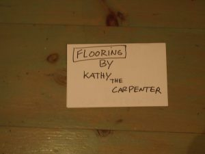 "Sign on floor reading ""Flooring by Kathy the Carpenter"""