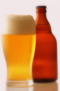 Light colored beer with frothy head and beer bottle.