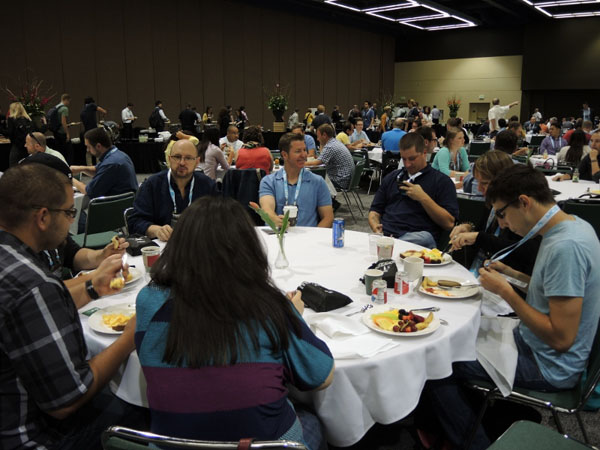 A round table with conference attendees eating lunch and networking.