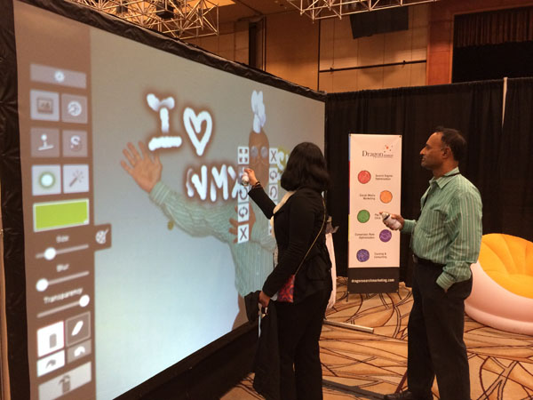 Conference attendees having fun drawing on the Graffiti board at the DragonSearch booth.