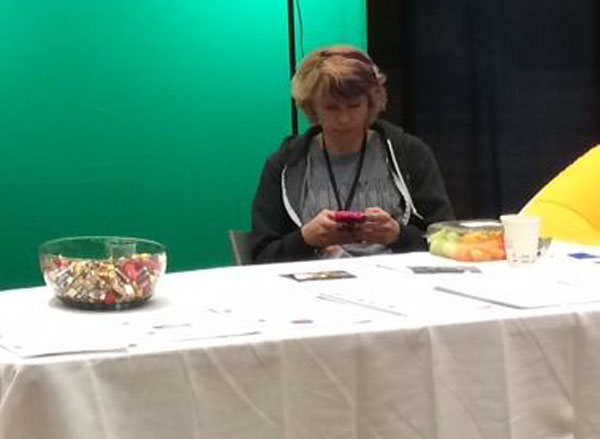 Bored looking person on their mobile phone sitting behind at table at a trade show.