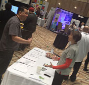 A man and women engaging at a conference booth