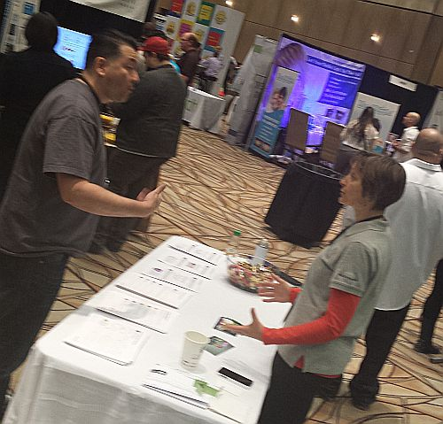 A man and a women engaging at a trade show table