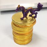 A stack of gold chocolate coins awarded to an intern; a purple dragon sits on top