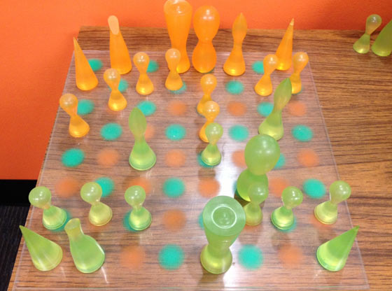 A chess board with orange and green pieces