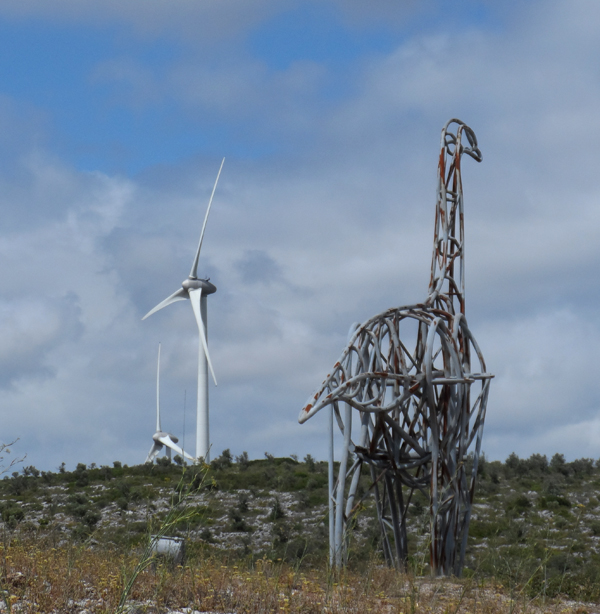 A metal dinosaur and wind turbine in a field set against a cloudy blue sky