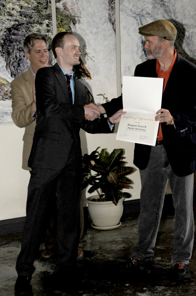 Tim Distel presenting a certificate of appreciation to Ric Dragon with Mayor Gallo in the back