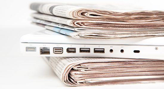 A laptop sandwiched between stacks of newspapers bridging traditional and non traditional marketing