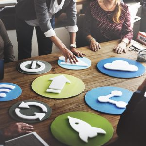 A team of social media marketers gathered around a table organizing channel icons