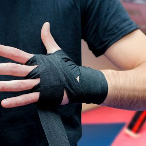 A man wraps support straps around his hands to prepare for a fitness routine