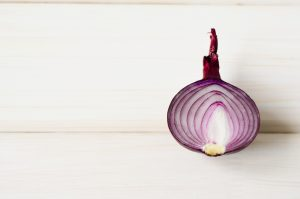 half a red onion on a wooden table