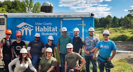 dragon360 team in front of habitat for humanity logo on trailer