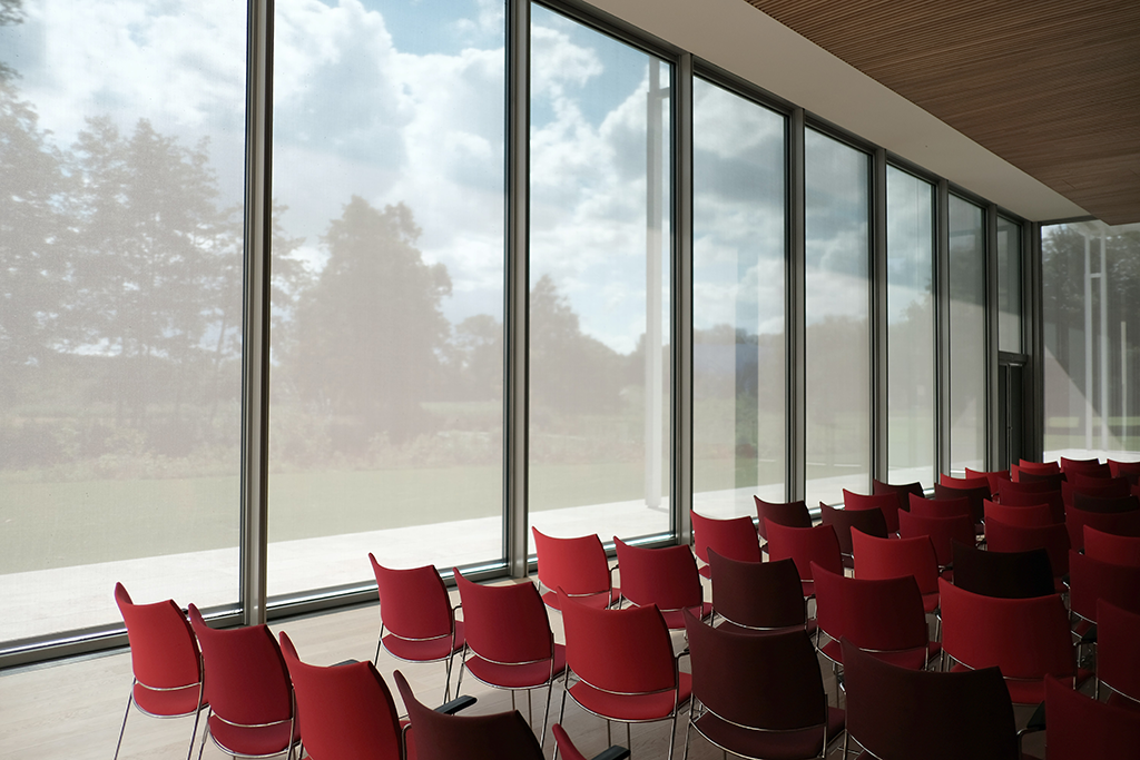 wide open conference room with floor to ceiling windows with red chairs