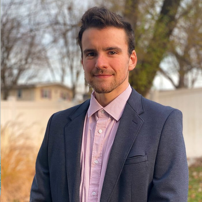 Brandon Pokedoff, Advertising Specialist, in a charcoal suit and pink button down